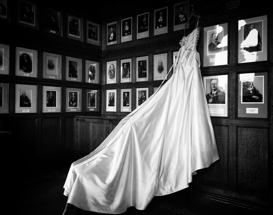 A wedding dress hanging before a wedding