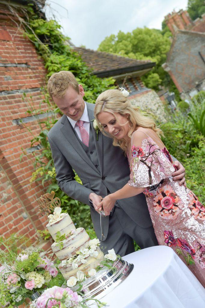 Couple cuts wedding cake outdoors