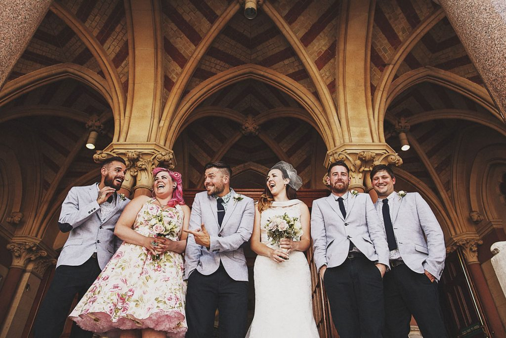 Bridal party laugh on front steps