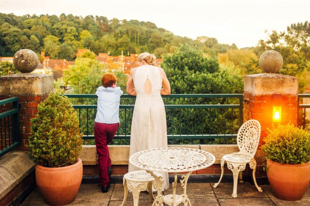 Bride stands on Walton balcony with young boy
