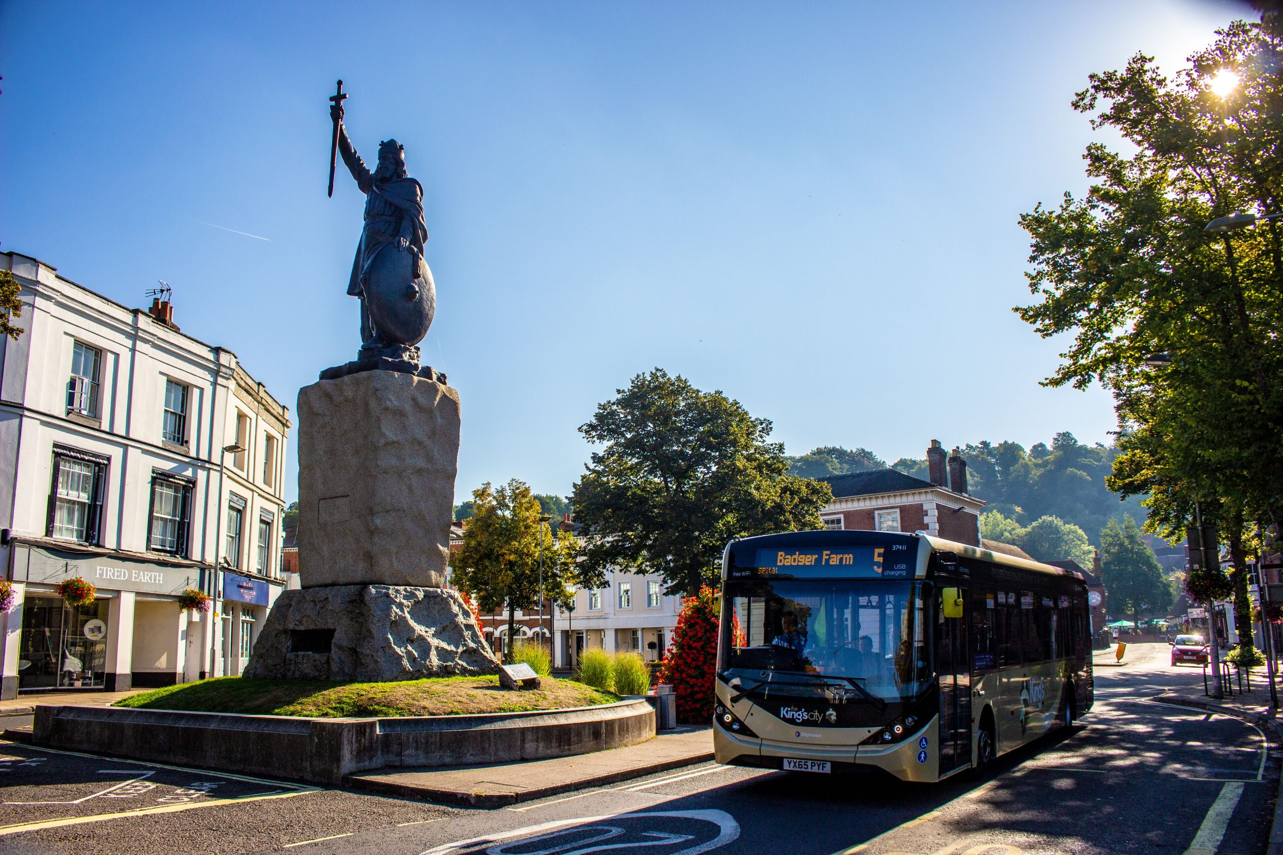 Photo of the King Alfred statue with a bus next to it